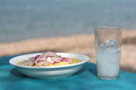 closeup greek traditional food fava with glass of ouzo by the sea with copyspace Stock Photo