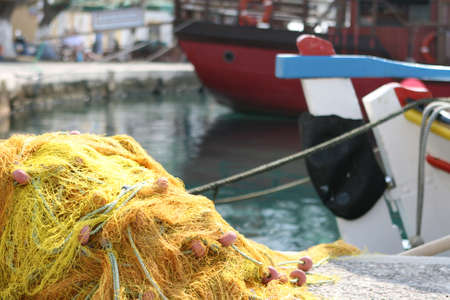 fishingnet: detail from  yellow fishingnet and boats background blur Stock Photo