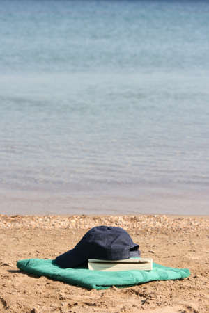 blue baseball hat on green towel by the see and book Stock Photo - 4074525