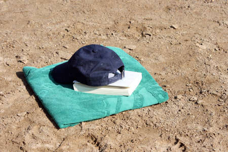 detail blue baseball hat on green towel  and book Stock Photo - 4078193