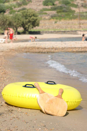 yellow inflatable by the sea and wooden beach tennis rackets with defocus people background