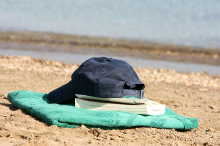 detail blue baseball hat on green towel by the see and book Stock Photo - 4078143