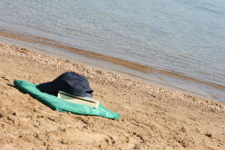 blue baseball hat on green towel by the see and book Stock Photo - 4078178