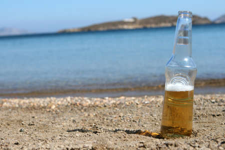 botle: one beer botle on the beach defocus sea and island background
