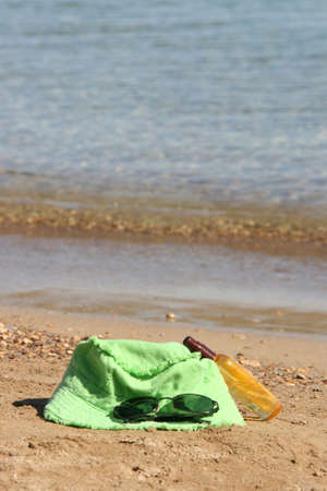 summer accessories green hat spectacles and sun oil by the sea Stock Photo - 4074513