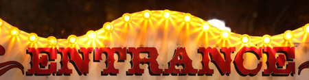 retro entrance sing with lights at night at amusement park Foto de archivo