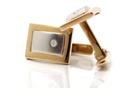 closeup Pair of gold cuff links with diamond isolated with reflection Foto de archivo