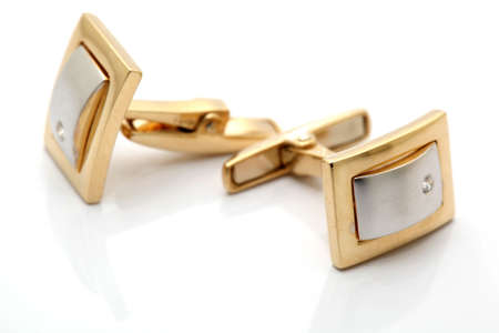 Pair of gold cuff links with diamond isolated with reflection