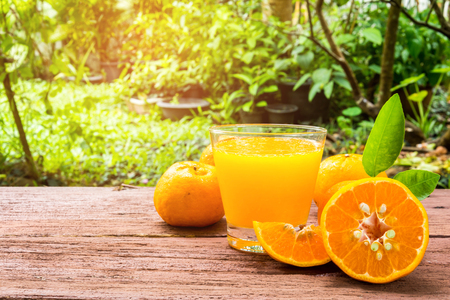 Orange juice on a wooden table in the backyard Stock Photo