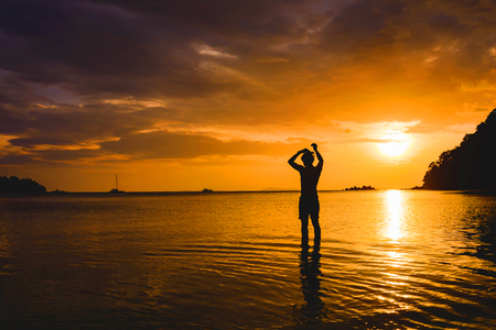Man standing in sea and sunset at the sea of Thailand