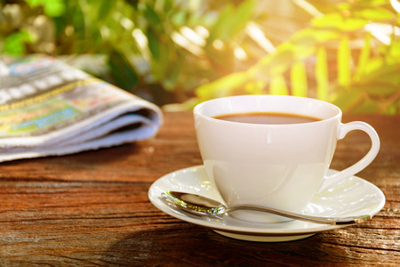 old desk: coffee cup clock and news paper on old wooden table the good morning Stock Photo