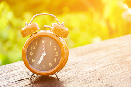 Brown clock on an old wood table Natural background Stock Photo