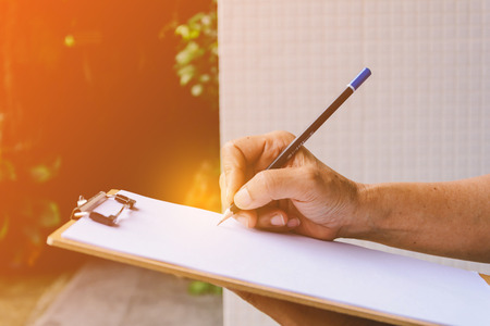 People are writing a message on it paper on clipboard at daytime Stock Photo