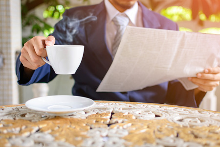 Male businessmen read newspapers and drank black coffee early in the morning at the home