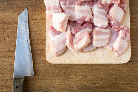 Raw pork on a cutting board wood table background .Food preparation procedure Stock Photo