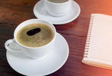 hustle: coffee cup clock and news paper on old wooden table nature background the good morning
