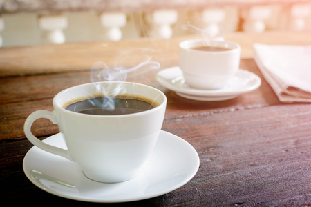 coffee cup clock and news paper on old wooden table nature background the good morning