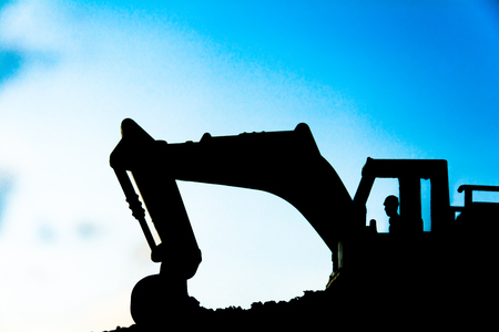 sand quarry: silhouette tracked excavator Sand and stone And sky background with toy car