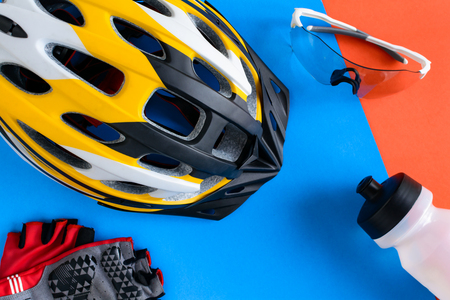 set bicycle equipment on a blue and orange paper background with healthy sports Stock Photo