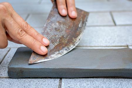 close up hand with Knife sharpener on rock tile background