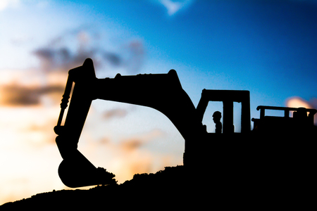 silhouette tracked excavator Sand and stone And sky background with toy car