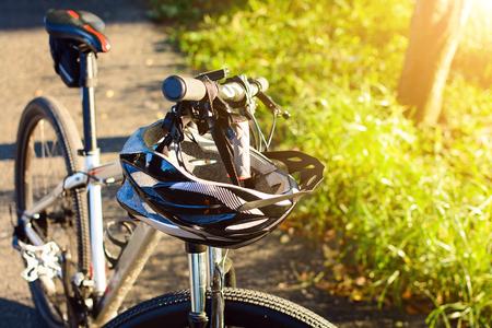 Bike helmet and bike on the street and evening sun