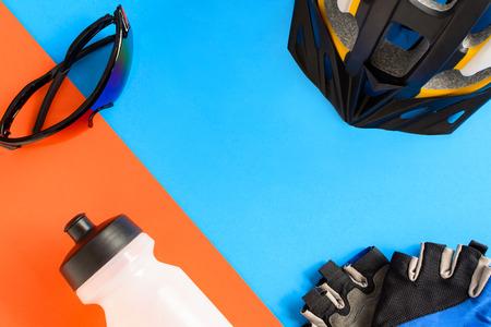 健康的なスポーツと青とオレンジの用紙の背景に自転車の機材をセットします。