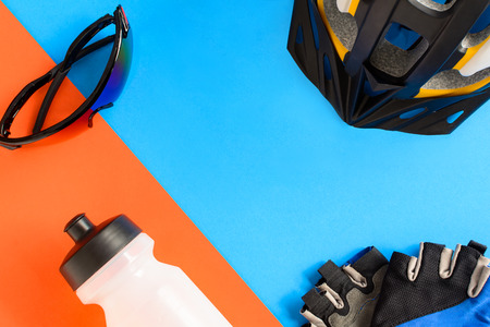 set bicycle equipment on a blue and orange paper background with healthy sports Foto de archivo