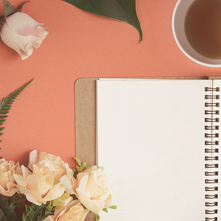 Flat lay Notebook and rose placed on a red desk with write text and vintage tone Stock Photo