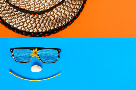 Sunglasses and hats on colorful blue and orange paper with Face smile and relax time