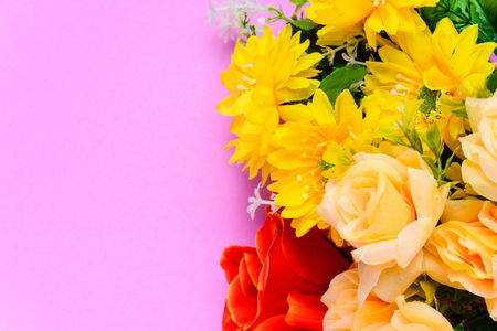 Flat lay fresh flowers on colorful paper with decor and design.