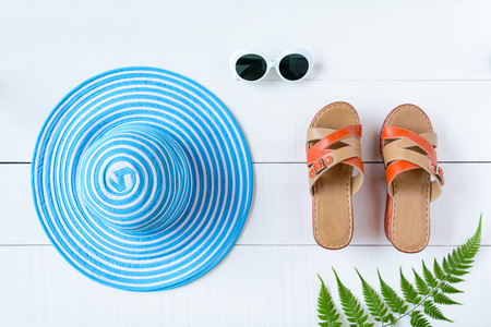 Blue hat sunglasses and shoe on white wood table with travel and fashion style Archivio Fotografico