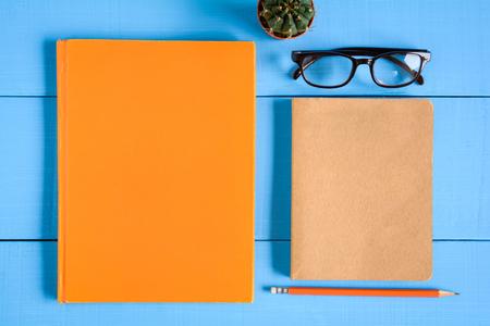 机の上にサボテンの装飾を持つ青い木のテーブルにトップビューの本のモックアップと鉛筆のノート