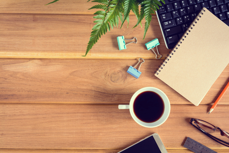 top view desk wood and office equipment with hot tea afternoon and decorative tree