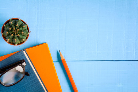 top view book mockup and pencil note on blue wood table with cactus decoration on desk