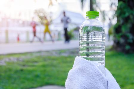 Plastic waterfles en witte doek op bureau met lopende lichaamsbeweging mensen in het park.