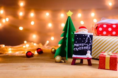 サンタ クロースと贈り物と木の板やクリスマス休暇と笑顔 kids.selective フォーカス暖かい光背景のボケ味のおもちゃ