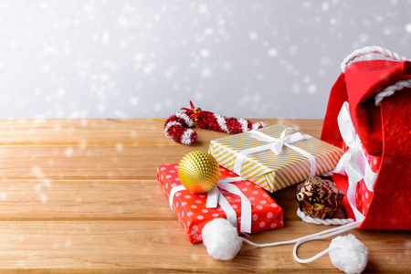 christmas and gift boxes in red bag and white background on wood table with the holiday season. shopping festival decoration