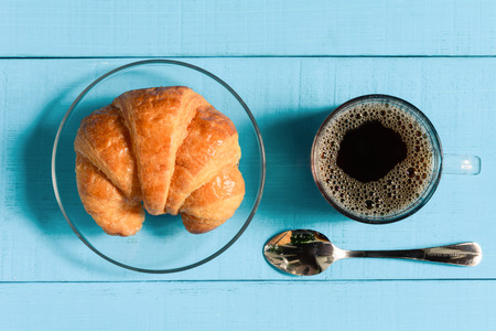 top view good morning black coffee cup and bread on a wooden table in the sunrise background. breakfast and wake up