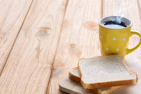 Good morning black coffee cup and bread on a wooden table in the sunrise background. breakfast and wake up Archivio Fotografico