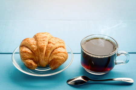 Good morning black coffee cup and bread on a wooden table in the sunrise background. breakfast and wake up Stock Photo