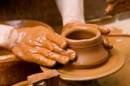 clay: Potter shaping a ceramic plate on a pottery wheel Stock Photo