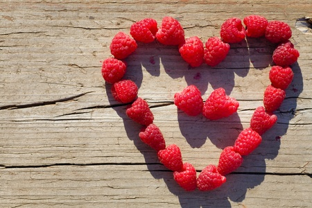 red Raspberry Heart  on wooden background in summer Banco de Imagens