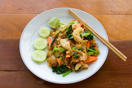 thai noodle with seafood on white plate with chopsticks photo