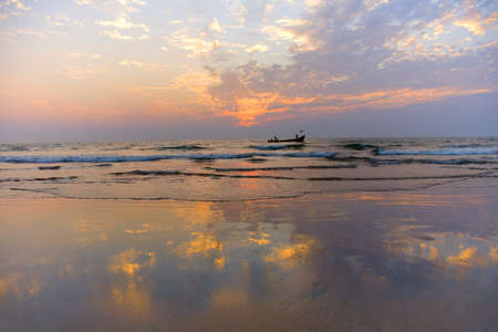 horizon reflection: GOA, INDIA - 23 NOV 2011:  indian boat  at sunset in the seaon Arambol beach in Goa Stock Photo