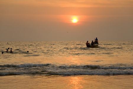 GOA, INDIA - 19 NOV 2011:  indian boat and swimming children at sunset in the seaon Arambol beach in Goa photo