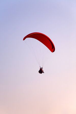 Paraglider final approach before landing in the evening sky photo