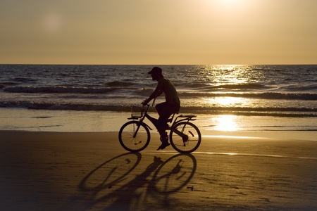 GOA, INDIA - 01 DEC 2011: Biker silhouette riding along beach at sunset on Arambol beach in Goa photo