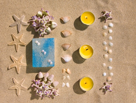 bar of natural handmade soap on sand with flower,  star and shell photo