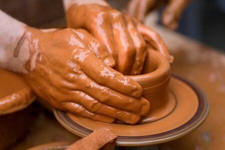 Potter shaping a ceramic plate on a pottery wheel photo